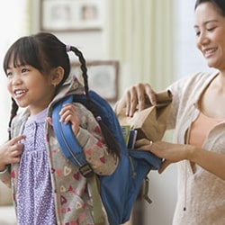 Mom packing child's backpack with food