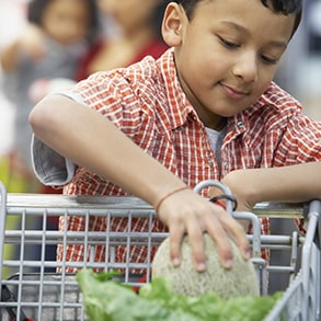Boy placing produce in shopping cart