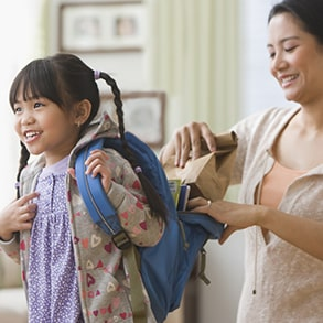 Mom placing sack lunch in child's backpack